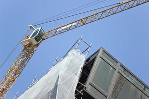 byggarbetsplats med kranar mot blå himmel foto