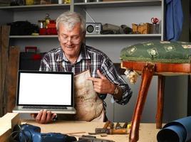 pensionerad snickare med bärbar dator foto