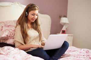 tonårsflicka liggande på sängen med bärbar dator bär hörlurar foto