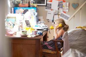 flicka sitter vid skrivbordet på föräldrarnas hemmakontor foto