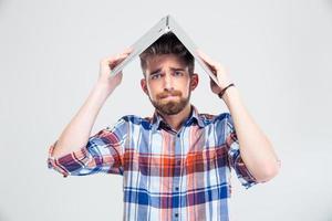 man håller bärbar dator på huvudet som tak av huset foto