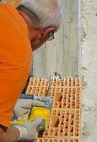 murare borrar ett hål med en kraftborr foto