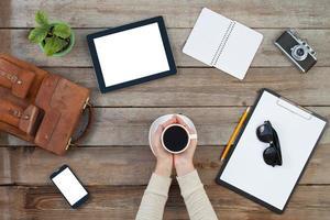 händer som håller en kopp kaffe med digital tablet PC foto