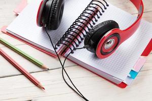 skrivbord med anteckningsblock och hörlurar foto
