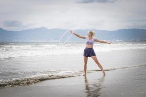 kvinnlig hoola-hoppartist på en strand i Mexiko. foto