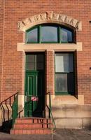 röd tegelvägg med en grön dörr och fönster foto