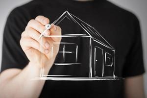 man ritar ett hus på virtuell skärm foto