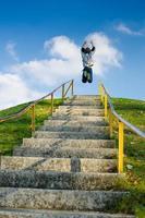 pojke hoppar ovanpå höga utomhus trappor foto