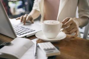 håller en kopp kaffe foto