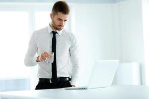 affärsman arbetar på sin dator på kontoret foto