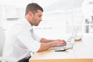 fokuserad affärsman som arbetar på sin bärbara dator foto