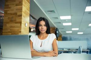 charmig affärskvinna som sitter vid bordet foto