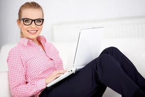 vacker kvinna som bär glasögon som kopplar av hemma foto
