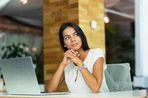 fundersam affärskvinna som sitter vid bordet foto