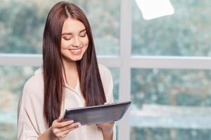 glad affärskvinna innehav bärbar dator foto