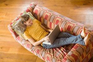 ung man använder laptop på sin soffa foto