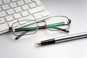 glasögon, penna och bärbar dator foto