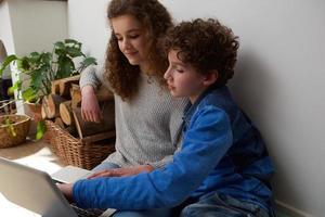 söt pojke och flicka som använder laptop tillsammans hemma foto