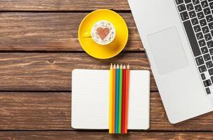 cappuccino och anteckningsbok nära bärbar dator foto