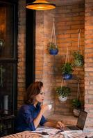 arbetar i mysigt kafé foto