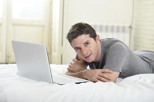 ung attraktiv man som ligger på sängen njuter av datorns sociala nätverk foto