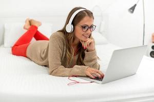 ung kvinna att skriva på laptop foto