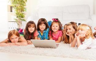 barn på golvet med laptop foto