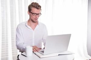 ung affärsman som arbetar på bärbar dator foto