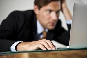 trött affärsman som arbetar på bärbar dator foto