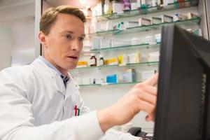 fokuserad farmaceut som använder datorn foto