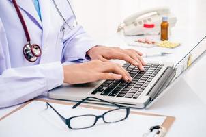 läkare skriver på datorn foto