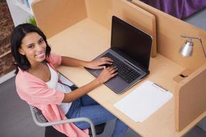leende kvinna skriver på sin dator foto