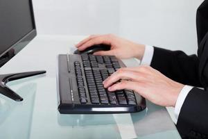 affärsman som använder datortangentbordet vid skrivbordet foto