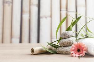 spa- och wellness-inställning med blommor, zenstenar och handduk foto