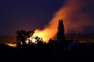 hög med hö i eld nära byn foto