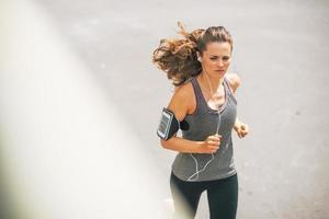fitness ung kvinna som joggar utomhus i staden foto