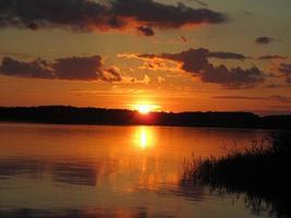 solnedgång över vatten, bruk och baltisk havshimmel brinner foto