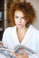 härlig lockig ung kvinna i vit badrock med magasinet foto
