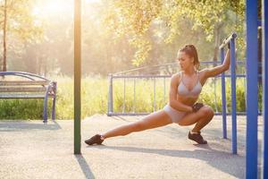 fitness tjej gör stretchövningar på sommaren utomhus foto