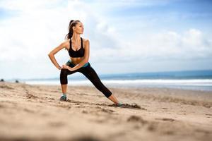 fit kvinna gör övningar för ben på stranden foto
