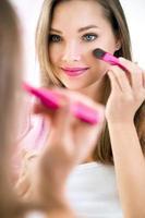 reflektion av ung vacker kvinna som applicerar hennes smink foto