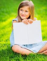 liten flicka som läser bok utanför foto