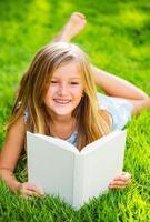 söt liten flicka läser bok utanför på gräset foto
