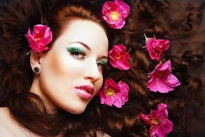 vacker brunett tjej med rosa blommor i håret. foto