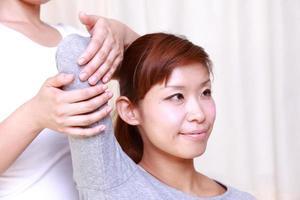 ung japansk kvinna som får kiropraktik foto
