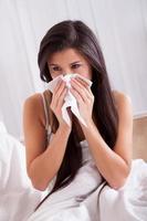 kvinna sjuk i sängen med förkylning och influensa foto