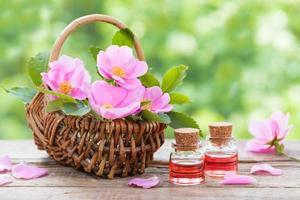 korg med rosa rosa höftblommor och flaskor olja