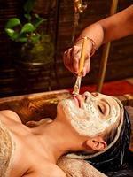 en kvinna som lägger sig i en handduk som bär mask på ayurveda spa foto