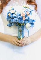 vacker ung brud som håller brudbukett med blå blommor foto