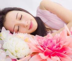 flicka i blommor som sover spa foto